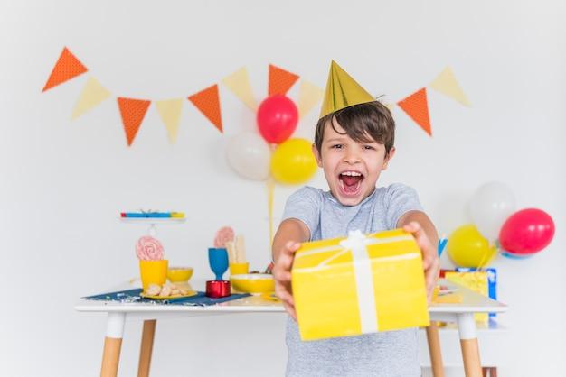 Muchacho alegre que toma la caja de regalo amarilla con la cinta blanca
