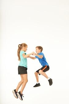 Muchacho alegre en ropa deportiva que toma las manos de la niña adorable mientras salta en el aire. aislado sobre fondo blanco