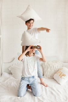 Muchacho con la almohada en la cabeza que apunta a algo mientras su hermana mira a través del telescopio