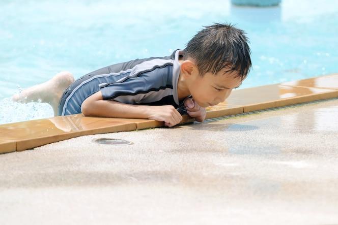 Muchacho asiático en traje de baño, diversión de natación en la piscina.