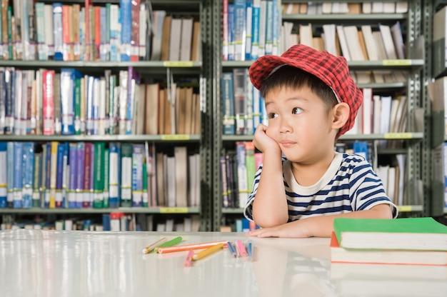 Muchacho asiático en la escuela de la sala de biblioteca
