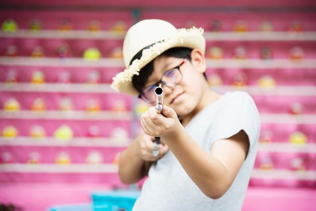 Muchacho asiático feliz jugando muñeca disparar pistola en evento de festival de parque de diversión local, personas con actividad feliz