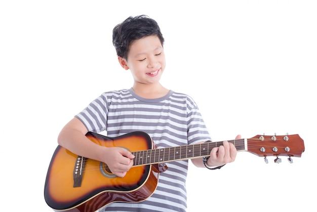Muchacho asiático joven que toca la guitarra y sonrisas sobre el fondo blanco