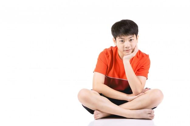 Muchacho asiático joven del retrato que se sienta sobre el fondo blanco,
