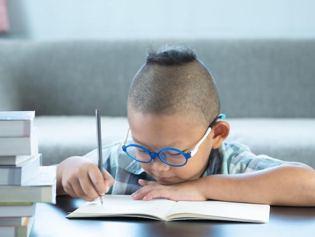 El muchacho asiático lindo escribe la preparación en casa. concepto de educación