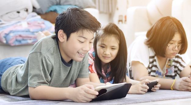 Muchacho asiático y muchacha que juegan al juego en el teléfono móvil junto con cara de la sonrisa.