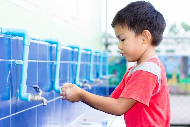 Muchacho asiático del niño que se lava las manos antes de comer la comida.