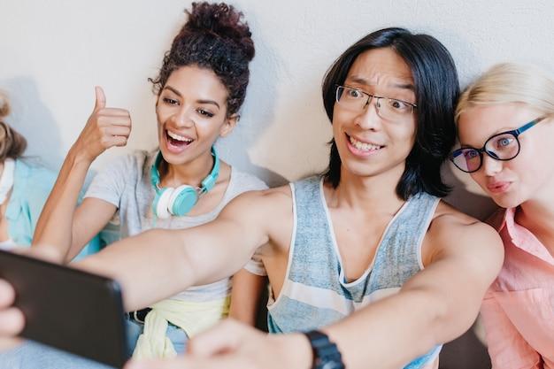 Muchacho asiático de pelo largo haciendo selfie con amigos sosteniendo un teléfono negro y sonriendo. mujer rubia divertida con gafas divirtiéndose con jovencita rizada y estudiante morena.