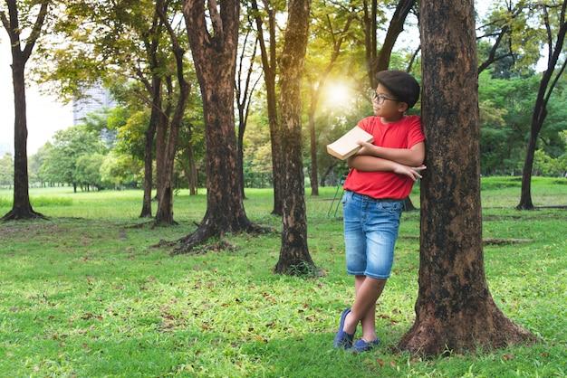 Muchacho asiático que se inclina contra el árbol grande en parque público, un libro a disposición