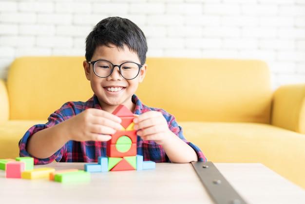 Muchacho asiático que juega el bloque de edificio colorido