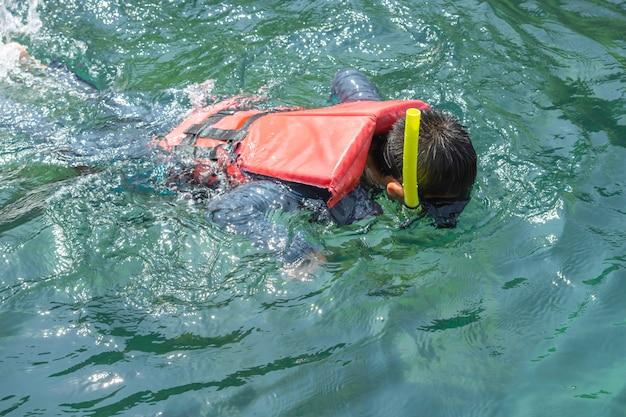 Muchacho asiático que lleva un chaleco salvavidas y el buceo en el mar.