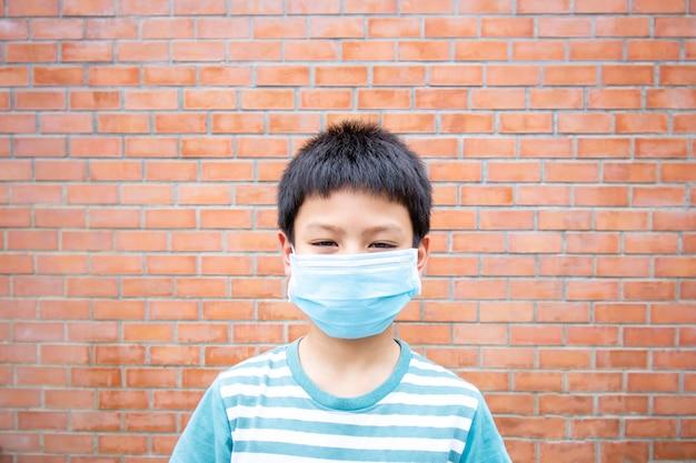 Muchacho asiático que lleva una pared de ladrillo del fondo de la máscara.