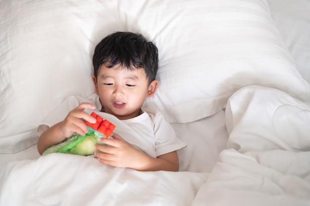 Muchacho asiático que miente y que juega en la cama blanca con la almohada y la manta