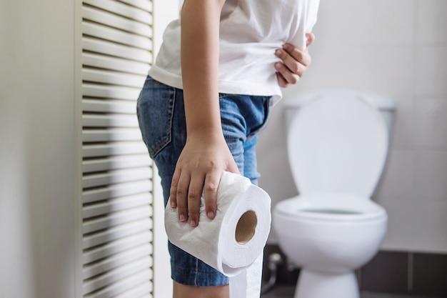 Muchacho asiático que se sienta en la taza del inodoro que sostiene el papel de tejido - concepto del problema de salud