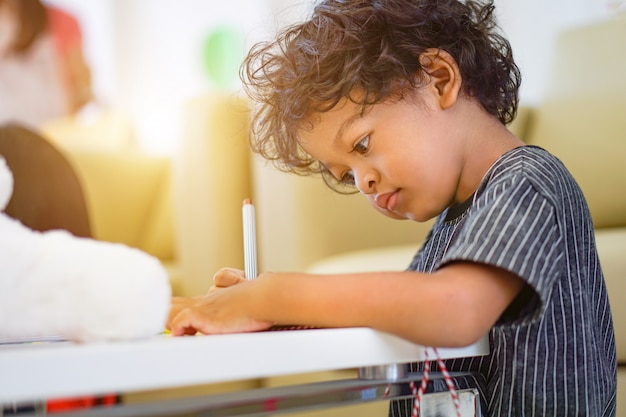 Muchacho asiático que usa una pluma mágica para escribir en el cuaderno y la luz de la tarde