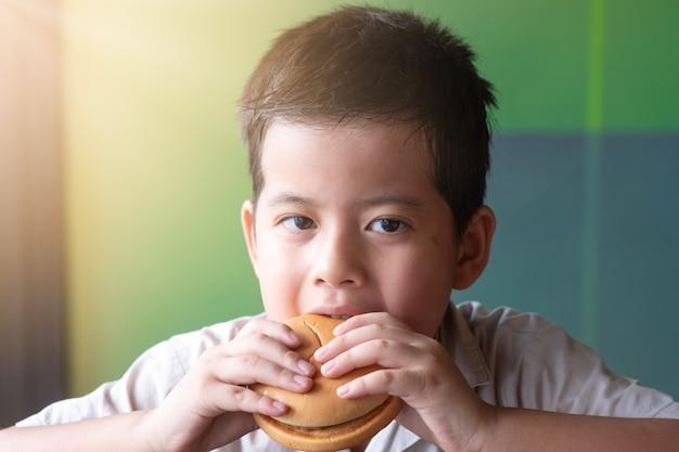 Muchacho asiático del retrato que está comiendo una hamburguesa. concepto de salud