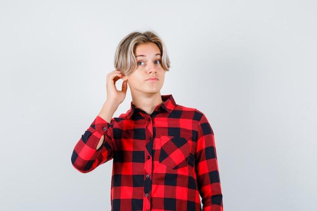 Muchacho bastante adolescente con la mano detrás de la oreja en camisa a cuadros y mirando curioso, vista frontal.