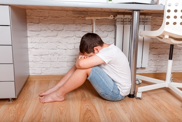 Muchacho caucásico joven del adolescente del preadolescente que abraza su rodilla, cubre su cara. cyber bullying en niños, salud mental infantil deprimida.