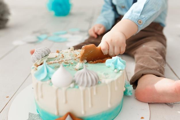 Muchacho de cumpleaños caucásico piernas y brazos mientras destruye y rompe su pastel de crema