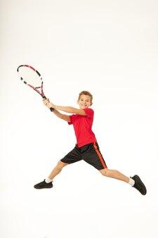 Muchacho deportivo lindo que sostiene la raqueta de tenis y que sonríe mientras salta en el aire. aislado sobre fondo blanco