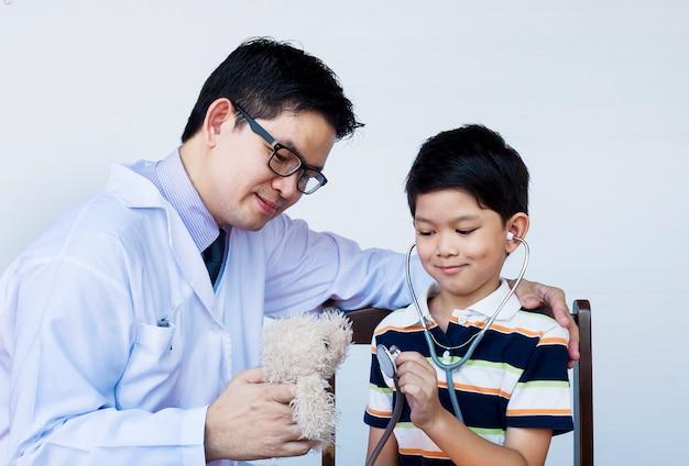 Muchacho y doctor asiáticos durante el examen usando el estetoscopio sobre el fondo blanco