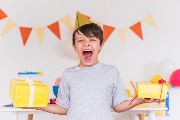 El muchacho emocionado con es boca abierta que lleva a cabo regalos de cumpleaños en la mano