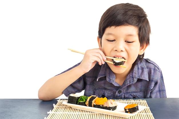 El muchacho encantador asiático está comiendo el sushi aislado sobre el fondo blanco