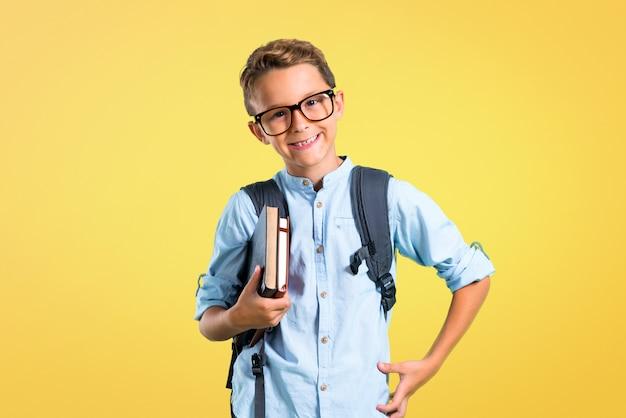 Muchacho del estudiante con la mochila y los vidrios que presentan con los brazos en la cadera en fondo amarillo.