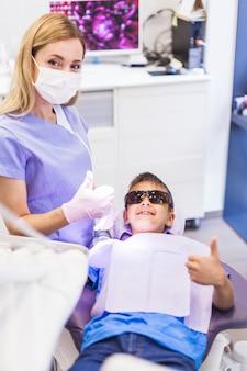 Muchacho feliz y dentista que gesticulan los pulgares para arriba en clínica