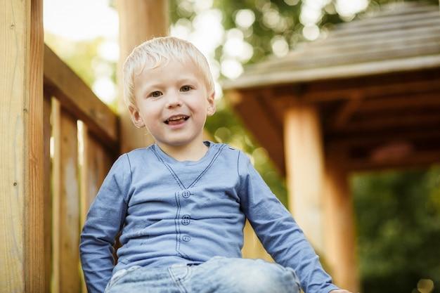 Muchacho feliz lindo con el pelo rubio que se divierte en el patio en día soleado de verano.