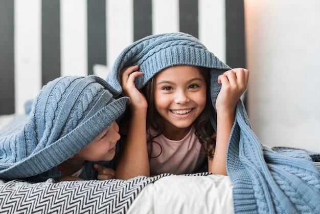 Muchacho feliz que mira a su hermana que miente debajo de la manta en cama