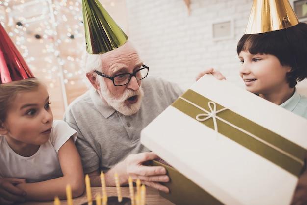 El muchacho de la fiesta de cumpleaños le da una caja al abuelo sorprendido.