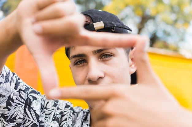 El muchacho joven adolescente hizo el marco de sus dedos
