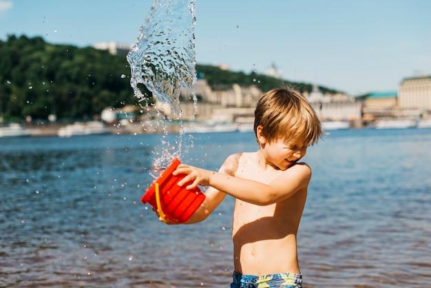 El muchacho joven derrama el agua del cubo en la playa del mar