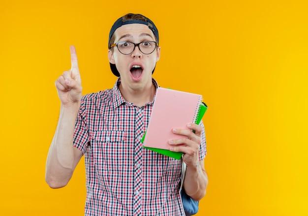 Muchacho joven estudiante sorprendido que lleva el bolso trasero y los anteojos y la tapa que sostiene el cuaderno y apunta hacia arriba en blanco