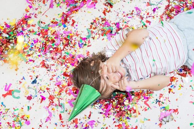 El muchacho joven explota el confeti, aislado en el fondo blanco