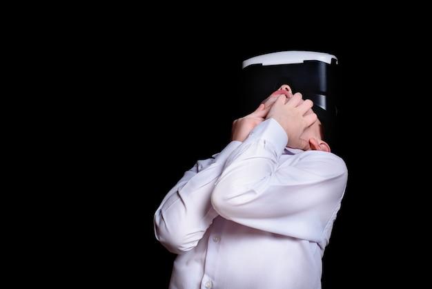 Muchacho joven con gafas de realidad virtual mira hacia arriba. camisa blanca. fondo negro