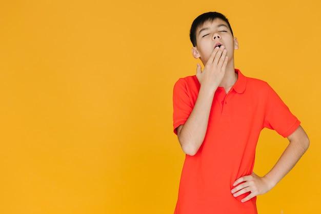 Muchacho joven que bosteza con el espacio de la copia