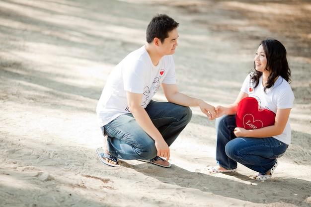 Muchacho joven que lleva a cabo su mano bonita de la novia en la playa