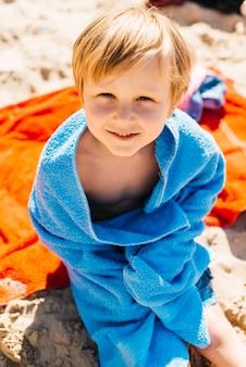 Muchacho joven que se sienta en la playa en toalla azul