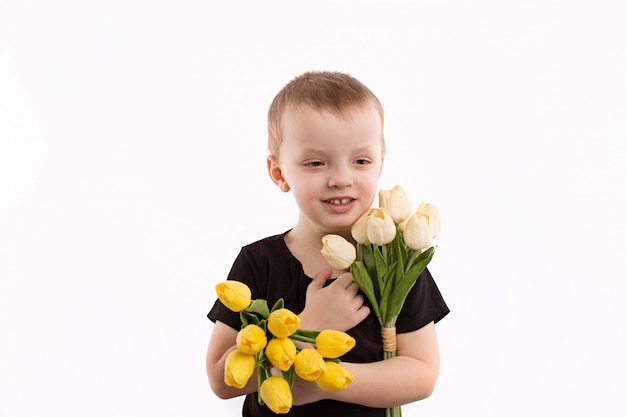 Muchacho joven que sostiene tulipanes aislados en blanco