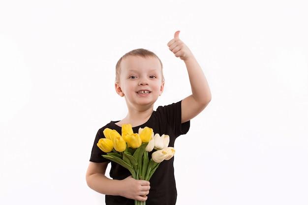 Muchacho joven que sostiene los tulipanes aislados en blanco
