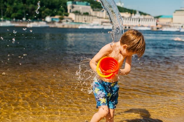 Muchacho joven que se vierte del cubo con agua en la playa del mar
