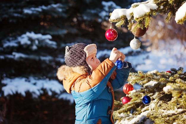 Muchacho lindo en clouth caliente y sombrero que coge la bola de la navidad en parque del invierno. los niños juegan al aire libre en el bosque nevado.