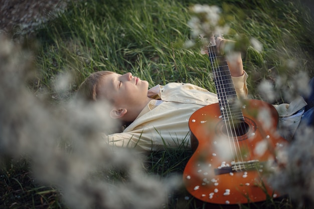 El muchacho lindo miente en la hierba con una guitarra en puesta del sol