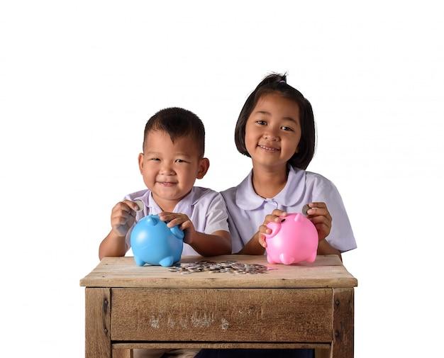 Muchacho lindo y muchacha asiáticos del país que ponen monedas en la hucha aislada en el fondo blanco