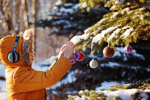 Muchacho lindo en paño caliente y sombrero que coge la bola de la navidad en parque del invierno. los niños juegan al aire libre en el bosque nevado. los niños atrapan bolas de navidad.