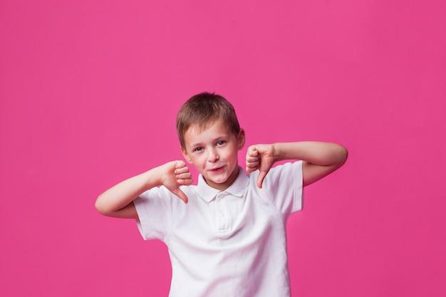 Muchacho lindo sonriente que muestra gesto de la aversión sobre la pared rosada