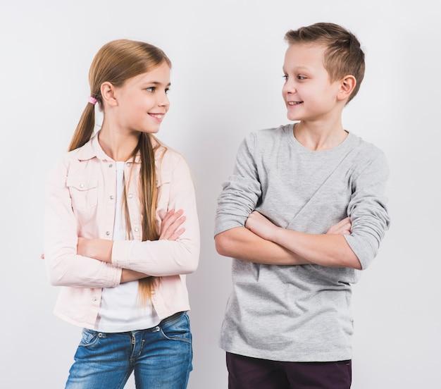 El muchacho y la muchacha sonrientes con los brazos cruzaron la mirada a la cámara contra el fondo blanco