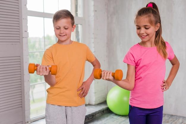 Muchacho y muchacha sonrientes con la mano en las caderas que ejercitan con pesas de gimnasia